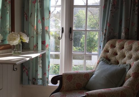 County interiors with soft floral furnishings at Penwartha Cottages