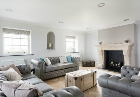 Coastal chic living space with pebble grey painted walls and classic chesterfields